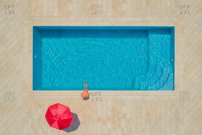 Aerial view of young girl in sunhat sitting by swimming pool and red parasol, Sumartin, Brac island, Croatia