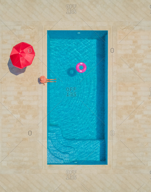 Aerial view of young girl in sunhat sitting by swimming pool with red parasol and inflatable ring, Sumartin, Brac island, Croatia