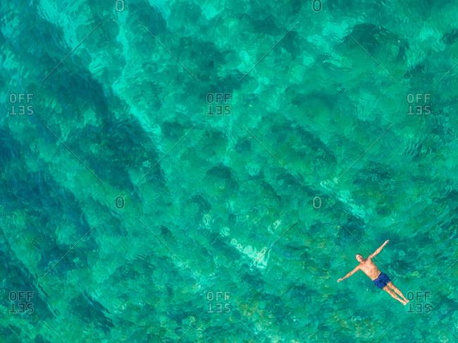 Aerial view of man floating in Adriatic sea, Sutivan, Brac island, Croatia