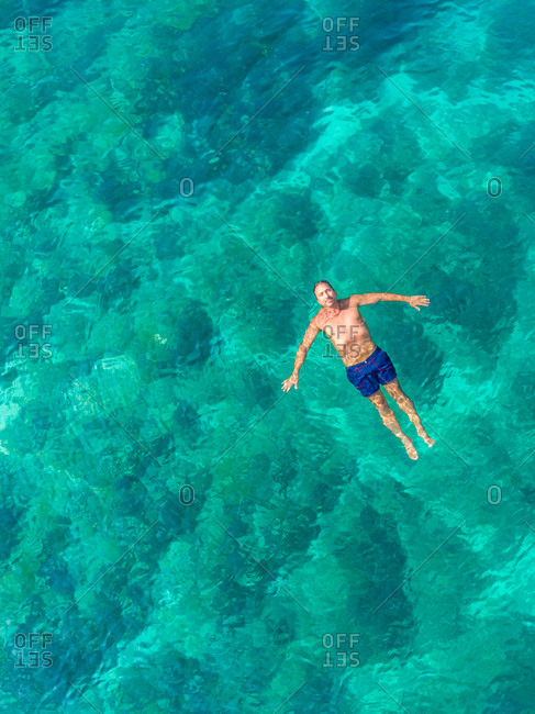 Aerial view of man floating in Adriatic sea, Sutivan, Brac island, Croatia