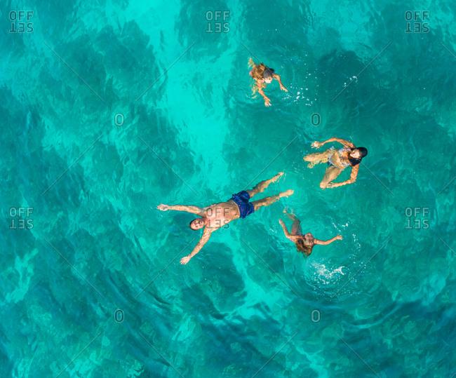 Aerial view of family of 4 swimming in turquoise Adriatic sea, Sutivan, Croatia