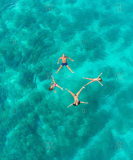 Aerial view of family of 4 playing in Adriatic sea, Sutivan, Croatia