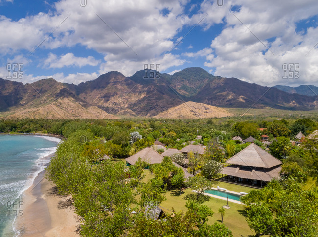 GEROKGAK, BALI - 21 AUGUST 2017: Aerial panoramic view of Puri Ganesha Homes with swimming pools by coast and mountains, Gerokgak, Bali