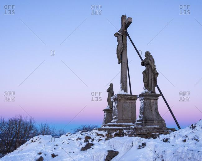 Cross with holy figures at dusk in winter, Milseburg, Danzwiesen, Rhoen Mountain, Hesse, Germany
