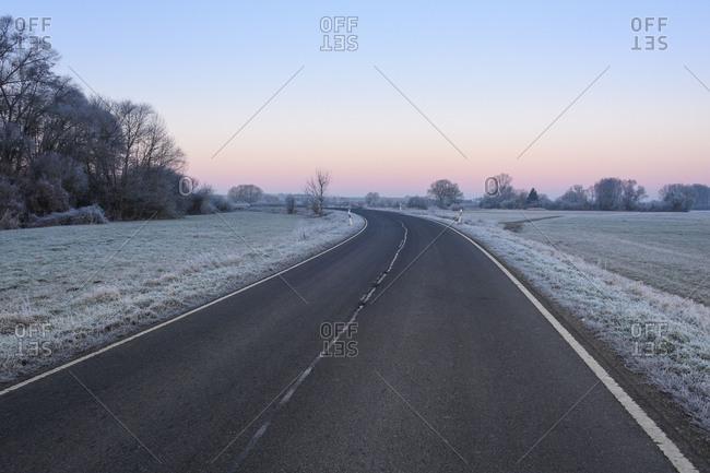 Road in winter landscape at dawn, Reinheimer Teich, Reinheim, Hesse, Germany