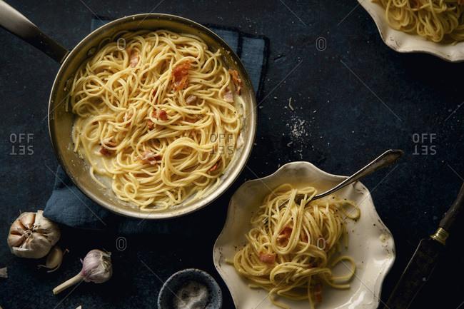Italian pasta carbonara with bacon on dark background