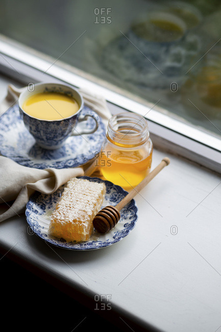 Homemade Turmeric Latte next to a window with honey