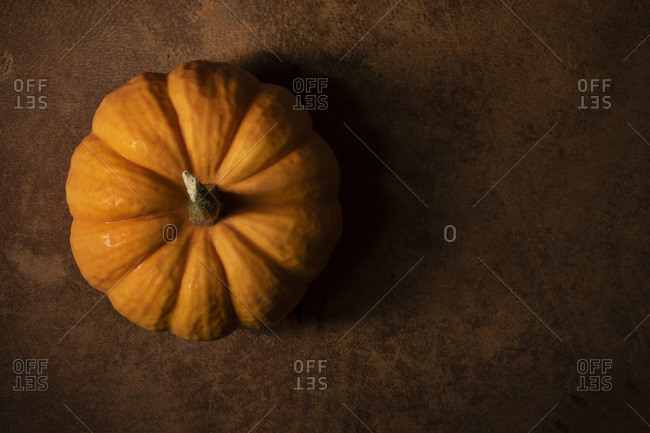 Mini orange pumpkin on a worn, leather surface. Moody natural lighting, overhead.
