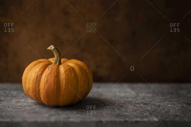 Mini orange pumpkin on a warn stone surface with rustic, brown, leather background. Moody natural lighting.