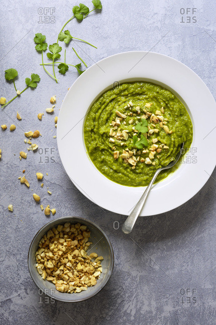 Broccoli soup in a bowl with a spoon and a bowl of crushed cashew nuts.