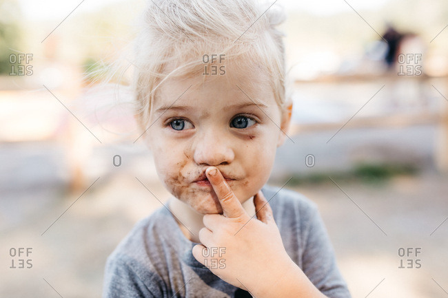 Portrait of a girl with a muddy face and her finger over her lips