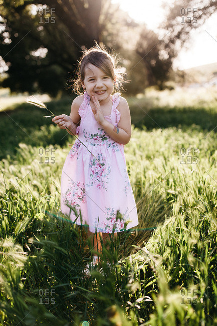 Smiling girl wearing a floral print dress standing in a meadow holding a stalk of wheat