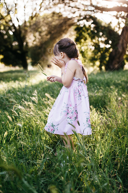 Side view of a girl wearing a dress standing in a meadow