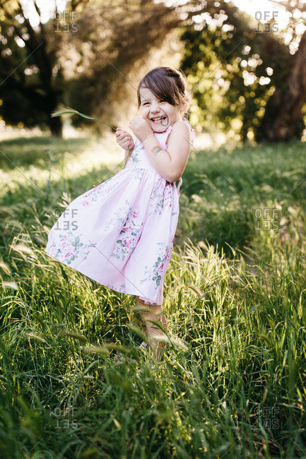 Smiling girl wearing a floral print dress standing in a meadow on a windy day