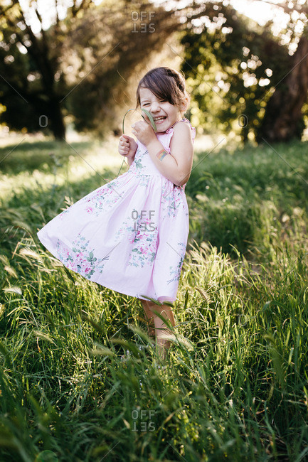 Laughing girl wearing a dress standing in a meadow on a breezy day