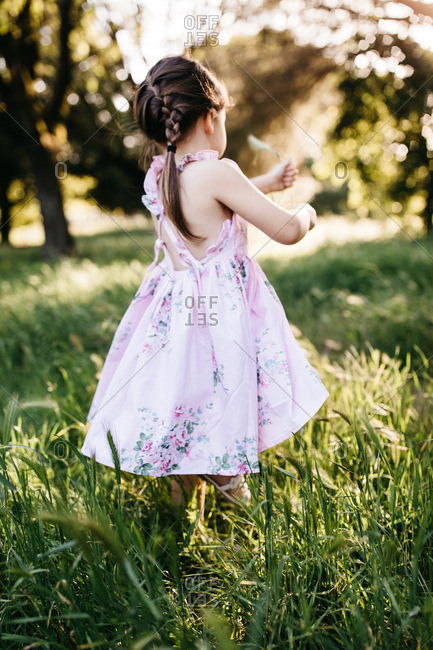 Back view of a girl wearing a floral print dress standing in a meadow