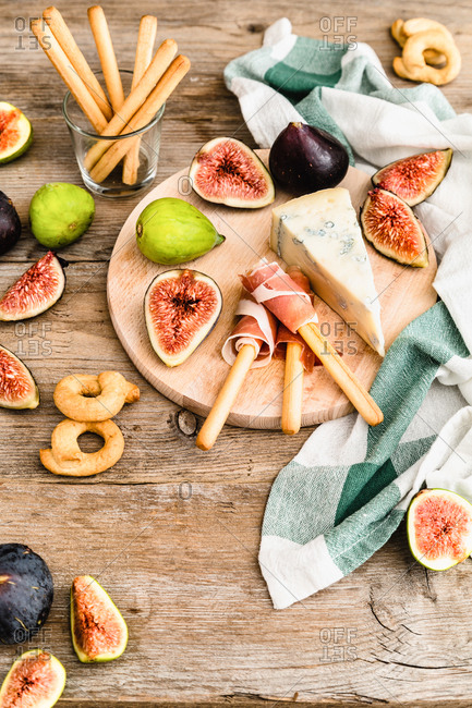 Fresh figs and gorgonzola cheese on wooden cutting board