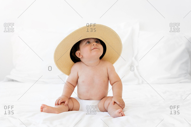 Chubby baby wearing hat and looking up