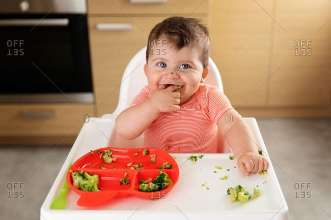 Smiling baby eating broccoli