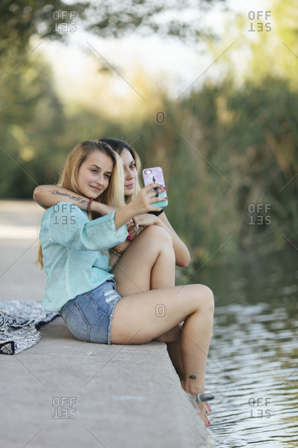 Two teen girls taking pictures on lakeshore