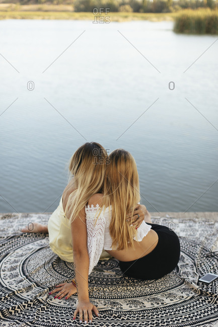 Rear view of two teen girls embraced on lakeshore
