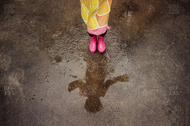 A girls shadow in a rain puddle