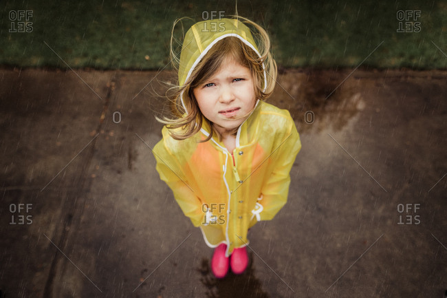 Little girl looking unhappy in the rain