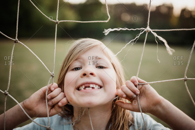 Little girl with her face in a soccer net