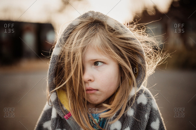 Little girl looking cold in a hooded jacket