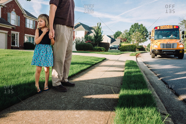 Little girl waiting for the bus with her father on the first day of school