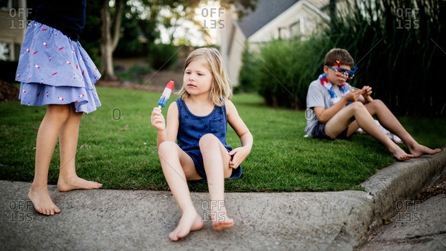 Little girl looking at her popsicle with her siblings in the front yard