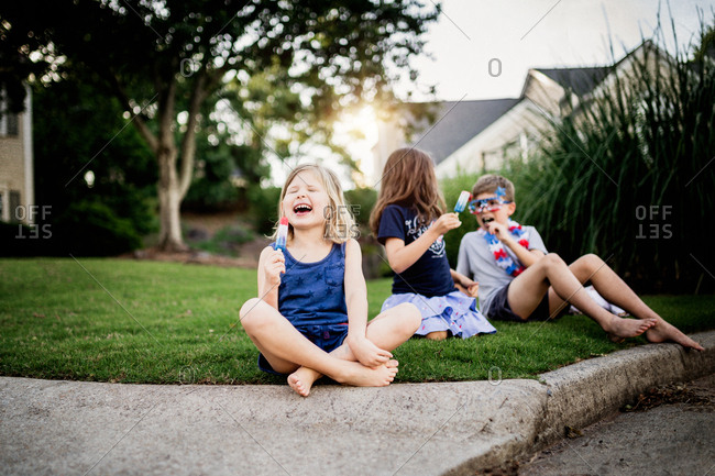 Little girl eating her popsicle with her siblings in the front yard