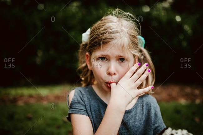 Little girl eating ice cream in the grass