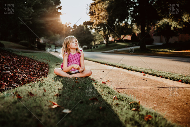 Young girl sitting on the sidewalk at sunset