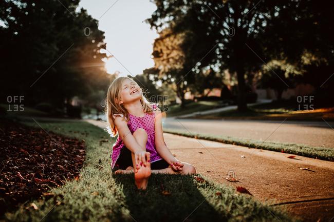 Little girl sitting on the sidewalk at sunset smiling
