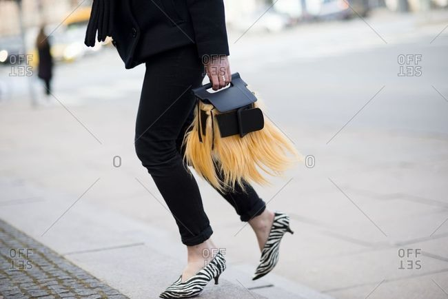 Copenhagen, Denmark - September 21, 2018: Woman wearing animal print shoes and carrying furry bag