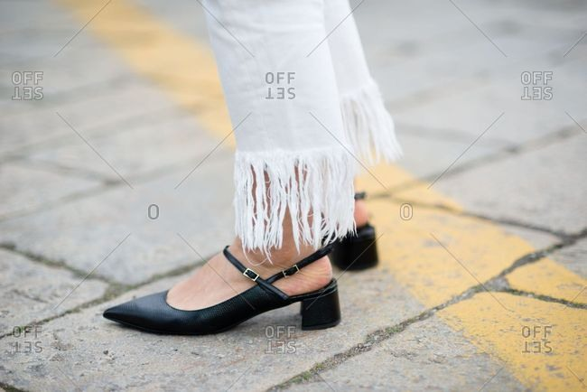 Woman wearing white fringe pants and black shoes