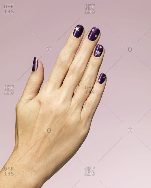 Woman's hand with purple star nail polish