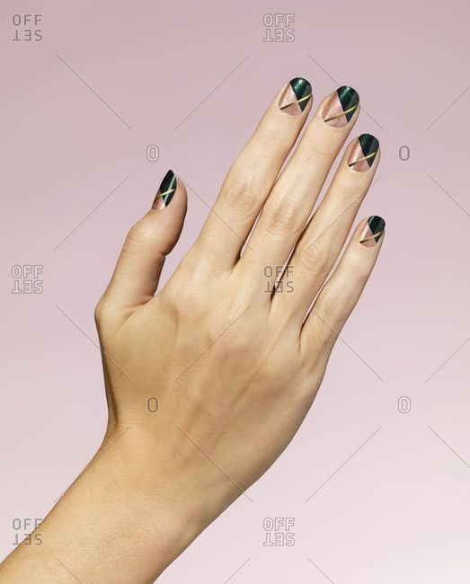 Woman's hand with green and gold nail polish