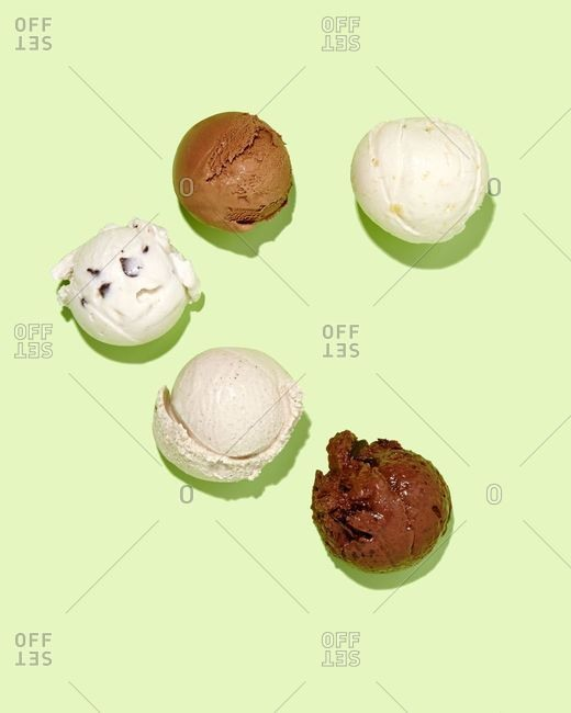Scoops of ice cream on green background