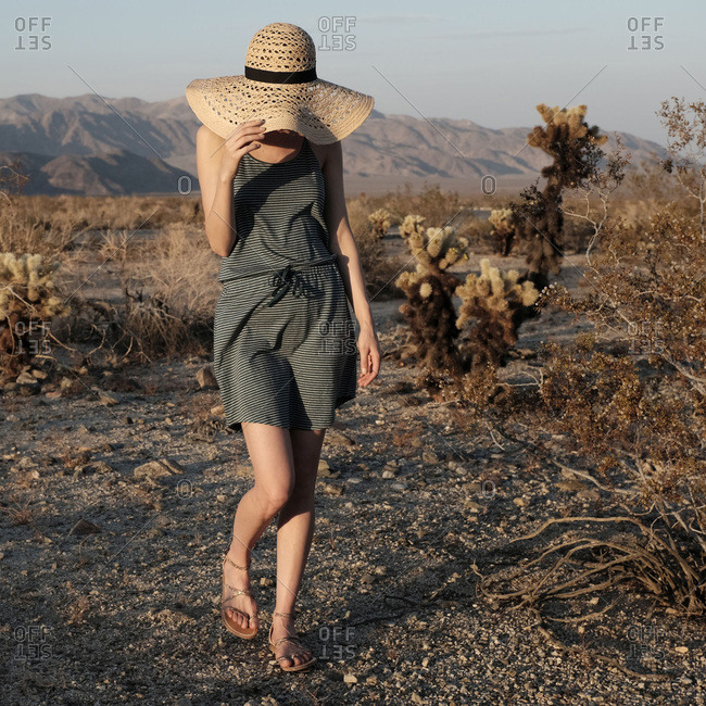 Woman walking at sunset wearing large hat