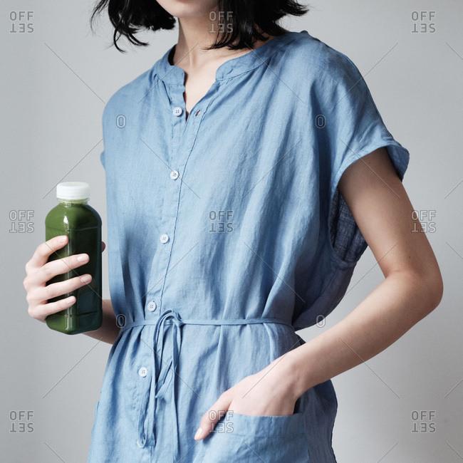 Woman holding green juice bottle