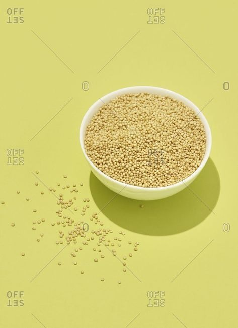 Bowl of dried quinoa on yellow background