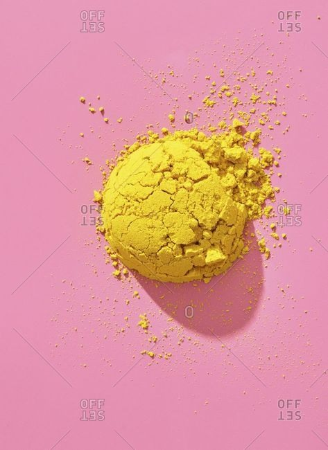 Pile of yellow powder on pink background