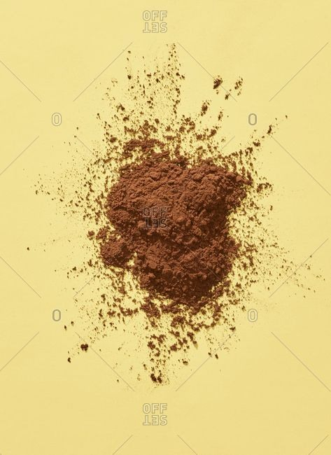 Pile of cocoa on yellow background