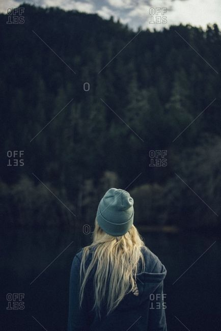 Rear view of blonde woman looking out at lake