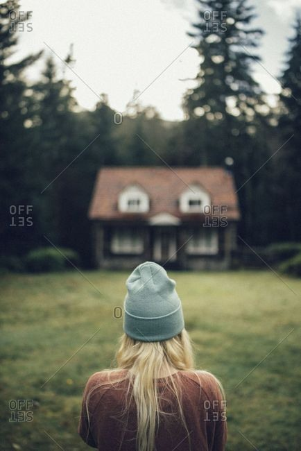 Rear view of blonde woman looking at small cabin in woods