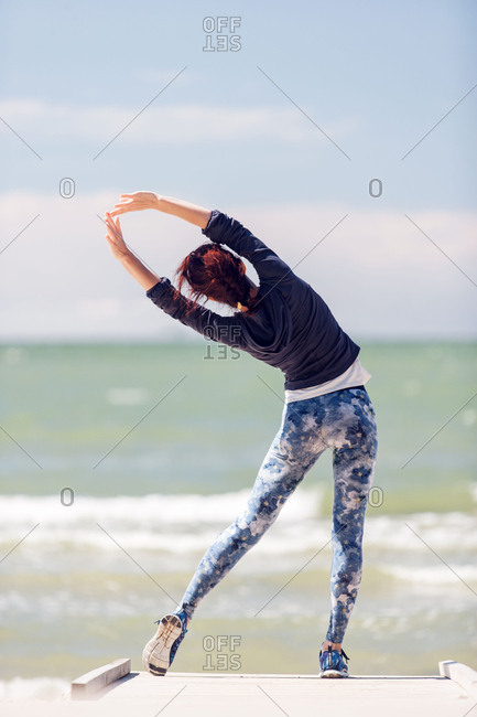 Woman stretching by the ocean during workout