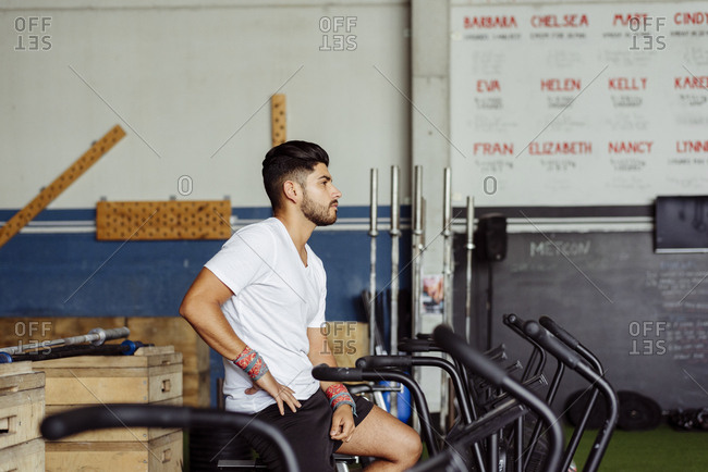 Handsome latin man recovering strength on the bicycle in the gym