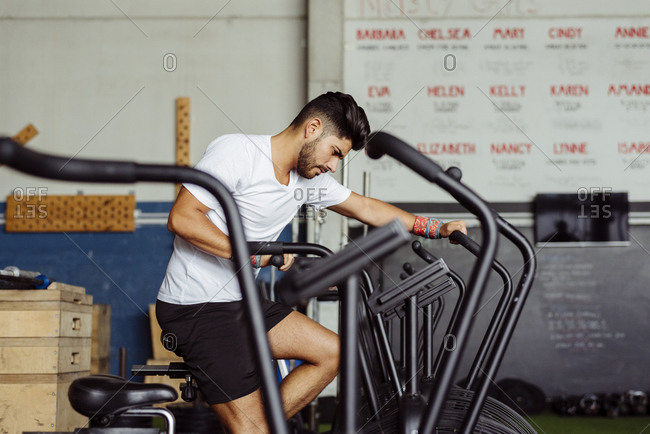 Handsome latin man exercising on the bicycle in the gym
